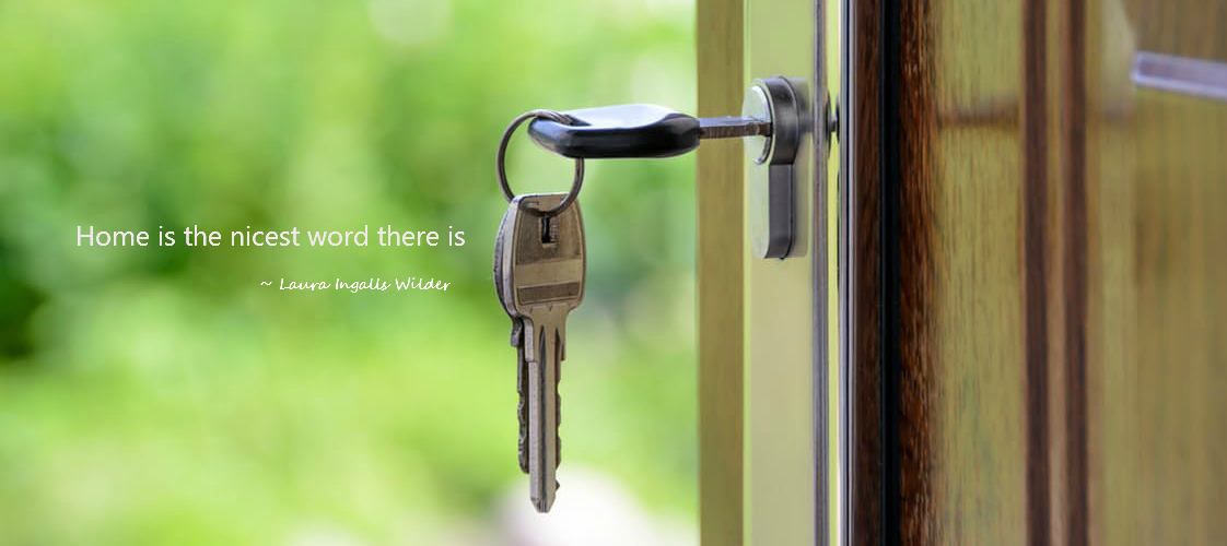 Keys in lock of open door, green foliage blurred in background.  Quote by Laura Ingalls Wilder, Home is the nicest word there is.